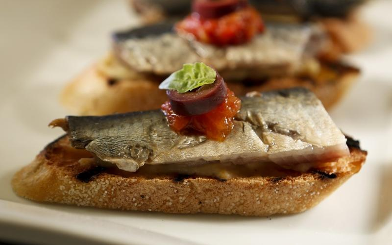 Pickled sardines on toast with artichoke puree, tomato and black olive